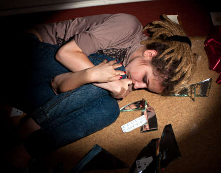 teenage problems. lonely, unhappy, sad girl lying on the dirty  floor in a dark room. Hard selective light. photo