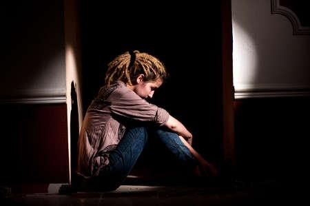 teenage problems: problemas de los adolescentes. chica solitaria, infeliz, triste sentada en un cuarto oscuro y sucio.