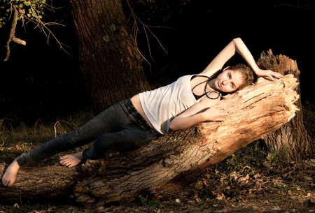 young girl in jeans and a white T-shirt lying on a fallen tree in  forest photo