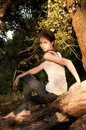 young girl in jeans and a white T-shirt sitting on a fallen tree in  forest photo