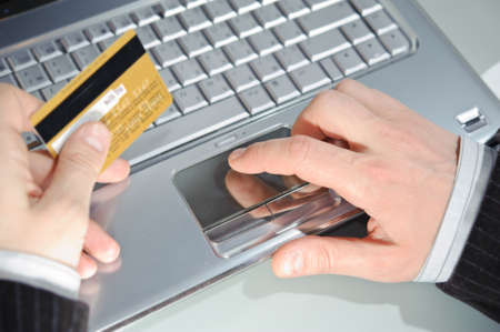 mans hand entering data using notebook while holding a credit card in the other hand  photo
