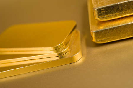 stack of pure gold ingots on a golden background Stock Photo