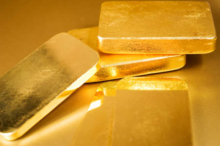 stack fine gold ingots on a golden background