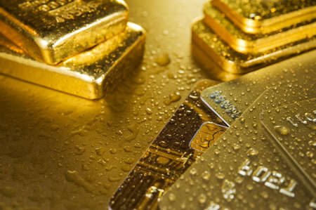 cashpoint: fine gold ingots and credit cards on a wet golden background