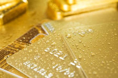 feinen gold Ingots und Kreditkarten auf nassen goldenen Hintergrund Standard-Bild