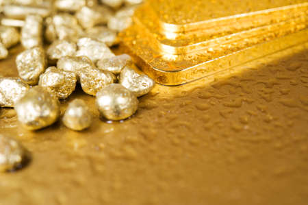 fine gold ingots and nuggets on a wet golden background Archivio Fotografico