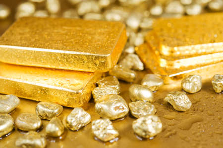 fine gold ingots and nuggets on a wet golden background photo