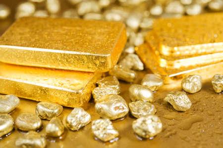 lingote oro: lingotes de oro finos y nuggets en un fondo dorado mojado
