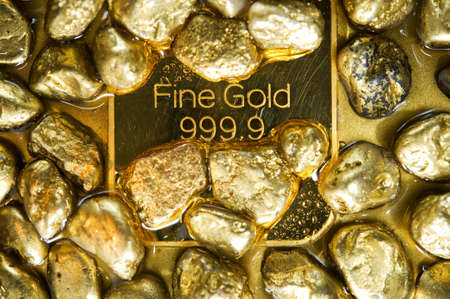 fine gold ingots and nuggets on a wet golden background Stock Photo