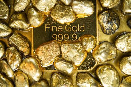fine gold ingots and nuggets on a wet golden background Foto de archivo