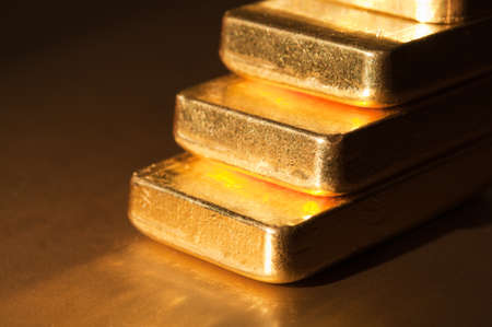 Stack fine gold ingots on a dark background. Stairs . Shallow depth of field. photo