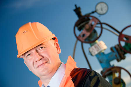 Oil worker in orange uniform and helmet on of background the valves, piping and sunset sky. Archivio Fotografico