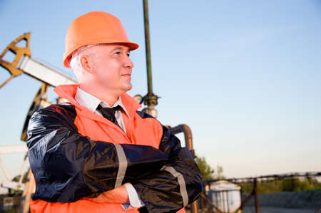 petroleum: Oil worker in orange uniform and helmet on of background the pump jack and blue sky.