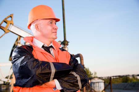 Trabajador petrolero en uniforme naranja y casco de fondo el conector de la bomba y cielo azul. Foto de archivo
