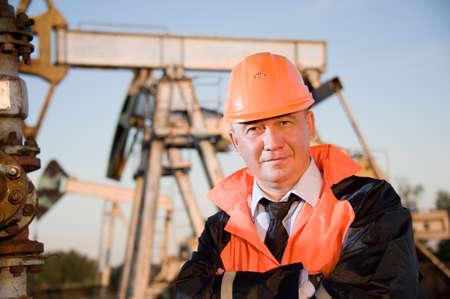 torre de perforacion petrolera: Trabajador petrolero en uniforme naranja y casco de fondo el conector de la bomba y cielo azul.