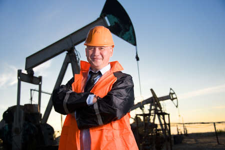 Oil worker in orange uniform and helmet on of background the pump jack and sunset sky. Stock Photo
