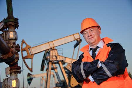torres petroleras: Trabajador petrolero en uniforme naranja y casco de fondo el conector de la bomba y cielo azul.
