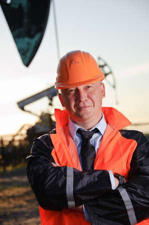 trabajador petrolero: Trabajador petrolero en uniforme naranja y casco de fondo el conector de la bomba y el cielo del atardecer.