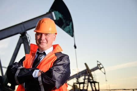 torres petroleras: Trabajador petrolero en uniforme naranja y casco de fondo el conector de la bomba y el cielo del atardecer.