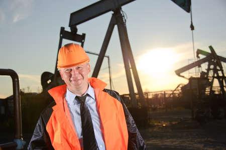 Oil worker in orange uniform and helmet on of background the pump jack and sunset sky. Foto de archivo
