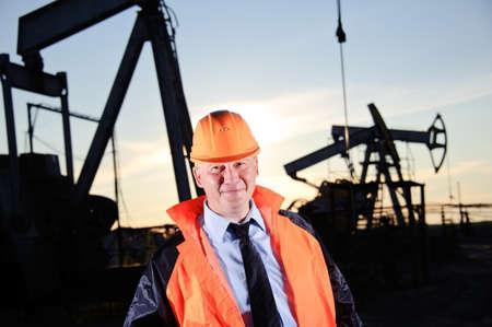 oil worker: Trabajador petrolero en uniforme naranja y casco de fondo el conector de la bomba y el cielo del atardecer.