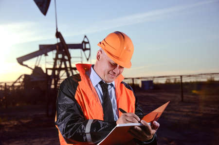Oil worker in orange uniform and helmet on of background the pump jack and sunset sky. Archivio Fotografico