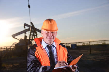 Oil worker in orange uniform and helmet on of background the pump jack and sunset sky. Look into the camera. photo