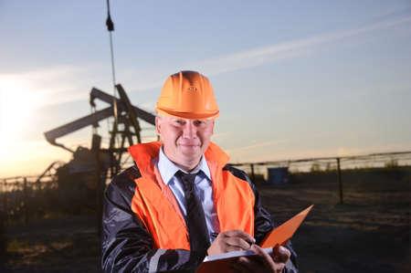 pozo petrolero: Trabajador petrolero en uniforme naranja y casco de fondo el conector de la bomba y el cielo del atardecer. Mira a la cámara.