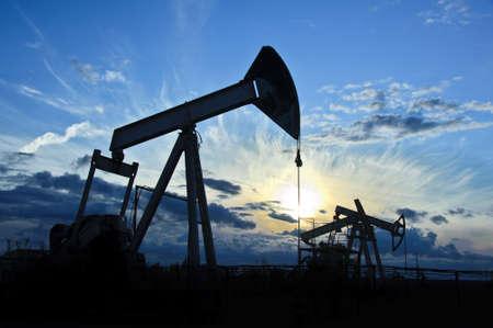 puits de petrole: pompes � huile sur le fond de ciel le coucher du soleil Banque d'images