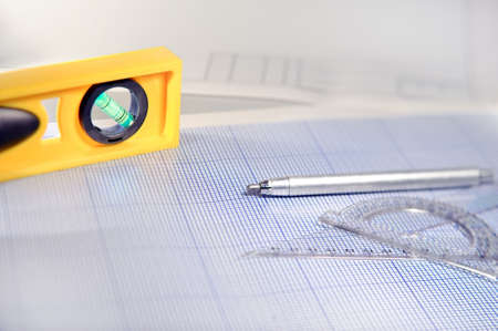 drafting tools: Pencil, graph paper, water level and ruler. Workplace Designer. Shot with shallow depth of field. Selective focus.
