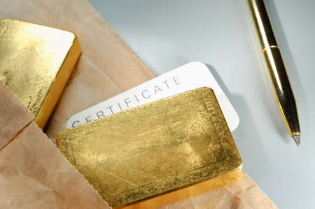 Processing and global trading of precious metals. Gold bars, certificate, pen and paper pack. Closeup. Stock Photo