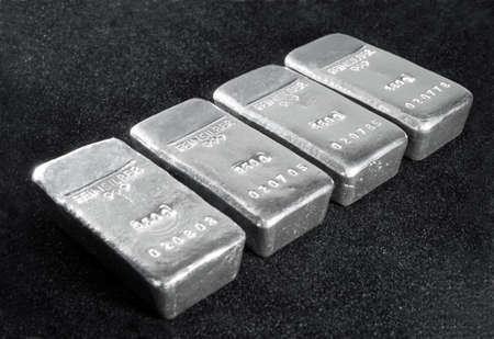 Processing and global trading of precious metals. Silver bars on a black background. Closeup. 免版税图像