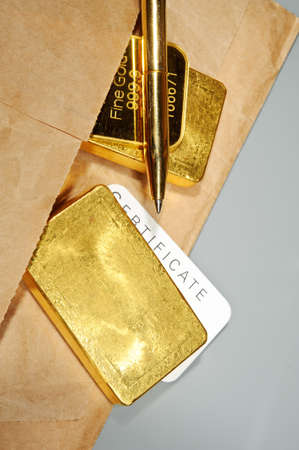 Processing and global trading of precious metals. Gold bars, certificate, pen and paper pack. Closeup. photo