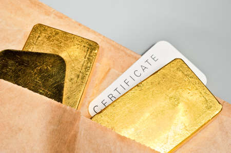 Processing and global trading of precious metals. Gold bars, certificate and paper pack. Closeup.