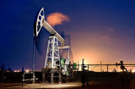 oil field: Oil pump-jack in action. Gas torches. Night view. Long exposure. Stock Photo