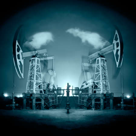 Two oil pump-jack in action. Night view. Long exposure. Toned. Stock Photo