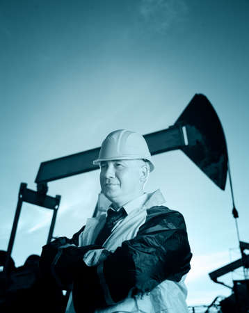 jack pump: Oil worker in uniform and helmet on of background the pump jack and sky. Toned. Stock Photo