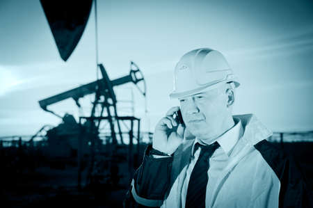 Oil worker in uniform and helmet, with mobile phone on of background the pump jack and sky. Toned. photo