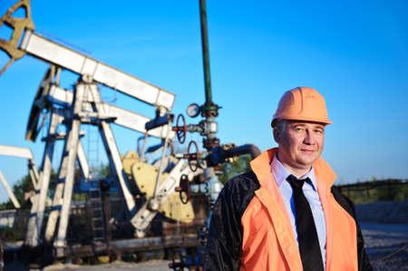 torre de perforacion petrolera: Aceite de los trabajadores en uniforme naranja y un casco en el fondo de la bomba de toma de cielo y el azul. Foto de archivo