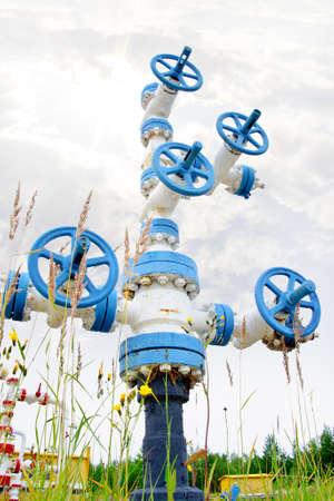 yacimiento petrolero: Petróleo, el gas. Boca de pozo con la armadura de la válvula en un fondo del cielo. Foto de archivo
