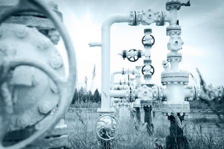Oil, gas industry. Group wellheads and valve armature on a sky background. Toned.