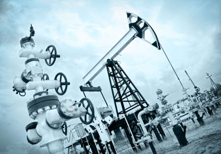 oilwell: Extraction of oil. Pump jack and oil wellhead. Toned. Editorial