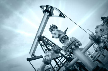 Extraction of oil. Pump jack and oil wellhead. Toned. Editorial