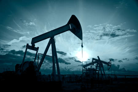 pompe: Industria petrolifera e del gas. Silhouette pompe dell'olio su uno sfondo cielo al tramonto. Tonica. Archivio Fotografico
