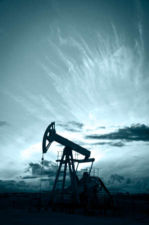 Oil and gas industry. Silhouette oil pump on a sunset sky background. Toned.