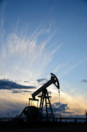 Oil and gas industry. Silhouette oil pump on a sunset sky background. Stock Photo