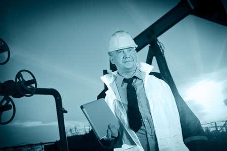 pozo petrolero: Aceite de los trabajadores en uniforme y casco en el fondo del cielo de la bomba de toma y puesta del sol. Entonado.