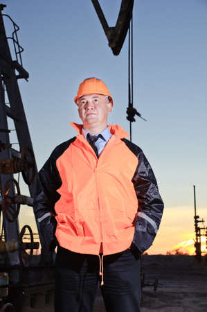 Worker in orange uniform and helmet on of background the pump jack and sunset sky. Severe. Hands in pockets. photo