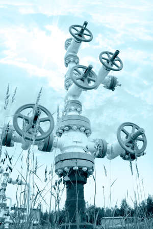 Oil industry. Wellhead with valve armature on a sky background. Toned.