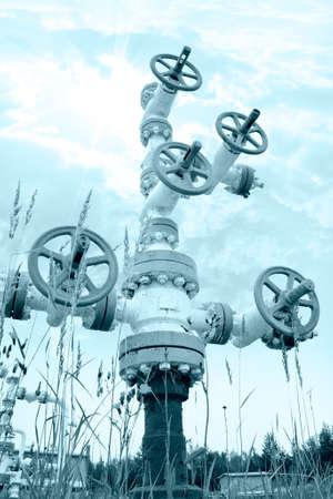 yacimiento petrolero: La industria petrolera. Boca de pozo con la armadura de la válvula en un fondo del cielo. Entonado.